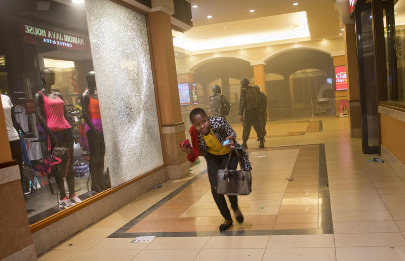 A woman who had been hiding during the gun battle runs for cover after armed police, seen behind her, enter the Westgate Mall in Nairobi, Kenya, on Saturday.