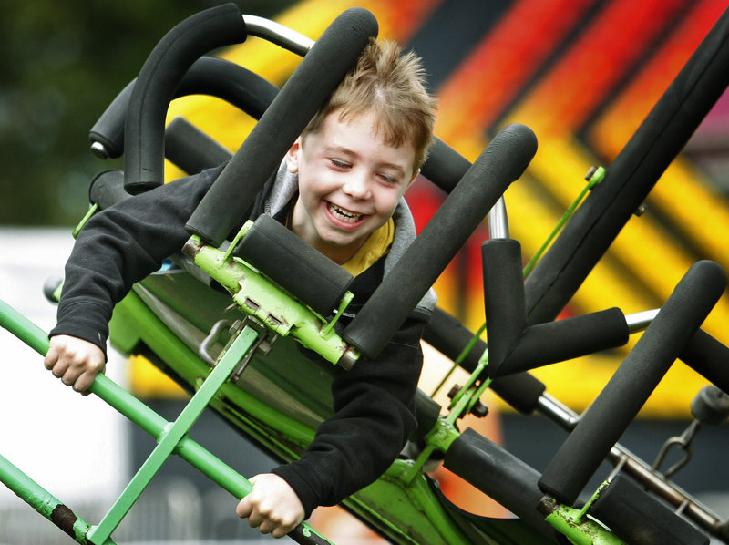 Ben Duda, 6, of Boston enjoys the wind and speed of flying on the Cliff Hanger ride on opening day at the Cumberland County Fair Sunday. Duda was visiting the fair with his grandfather, Fred Miller of Freeport.