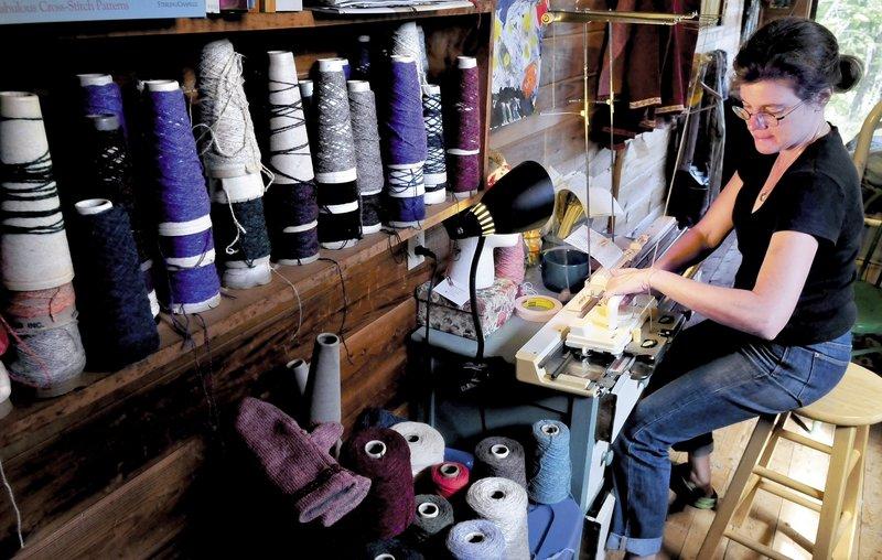 Karen Schorr operates her hand-powered knitting machine at her home in New Sharon. Schott will display her knitting machine and skills at the Lewiston/Auburn Mini Maker Faire on Saturday.