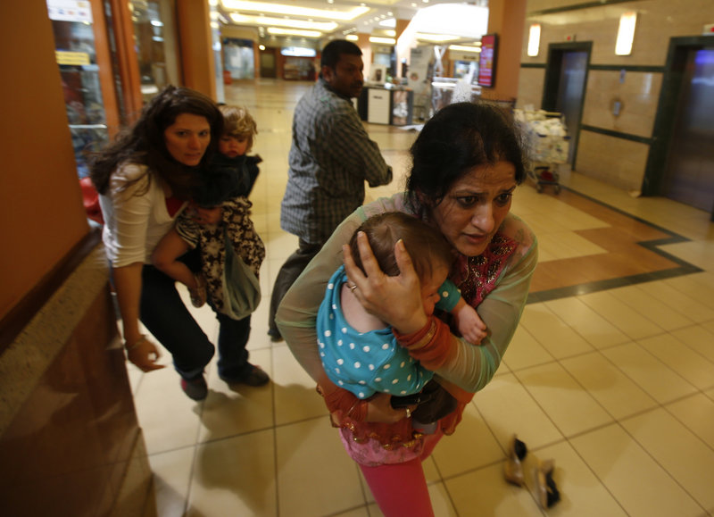 Women with children run for safety Saturday as police hunt the 10 to 15 armed militants who stormed the Westgate shopping centre in Nairobi. On Sunday, the military raided the mall to rout the gunmen.