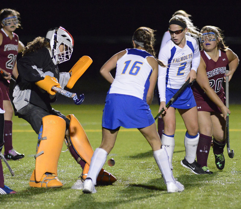 Freeport goalie Morgan Karnes makes a save as Mikey Richards, center, and Jillian Rothweiler look for the rebound during Falmouth's 4-0 home victory Monday night in a Western Maine Conference field hockey game.