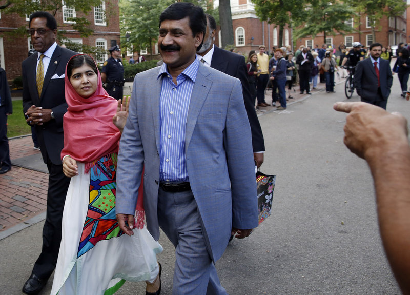 Malala Yousafzai waves to onlookers as she walks with her father, Ziauddin Yousafzai, right, and Director of the Harvard Foundation and Professor of Neurology at Harvard Medical School Dr. S. Allen Counter, through Harvard Yard after a news conference on the campus in Cambridge, Mass. on Friday, Sept. 27, 2013. The Pakistani teenager, an advocate for education for girls, survived a Taliban assassination attempt in 2012 on her way home from school. (AP Photo/Jessica Rinaldi)