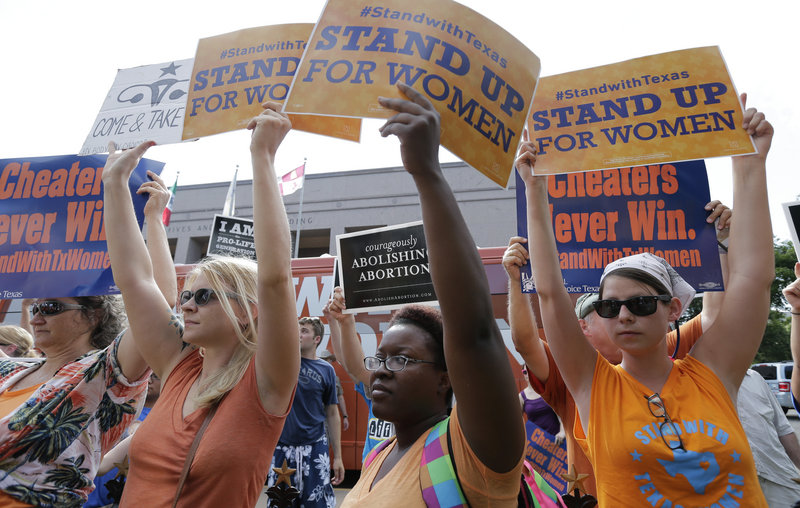 Opponents and supporters of a new, more strict abortion bill hold signs in Austin, Texas, earlier this summer. On Friday, a coalition of health-care providers in Texas filed a lawsuit to block the law as unconstitutional.