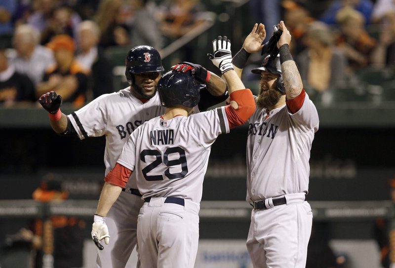 Daniel Nava is greeted by teammates David Ortiz, left, and Mike Napoli after his first-inning home run that sent the Red Sox well on their way to an easy win at Baltimore on Friday night.