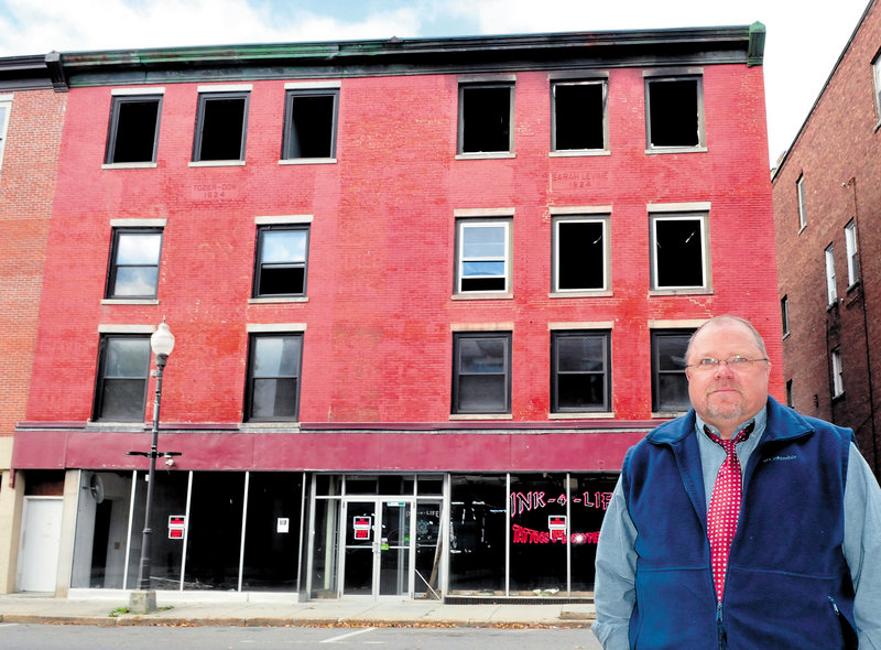 Building owner John Weeks stands in front of the apartment building on Main Street in Waterville that was destroyed by fire last May. Weeks says he plans to raze the structure and possibly build another at the site.