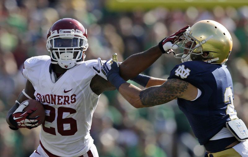 Damien Williams of Oklahoma tries to break away from Notre Dame's Bennett Jackson during Oklahoma's 35-21 win Saturday at South Bend, Ind.