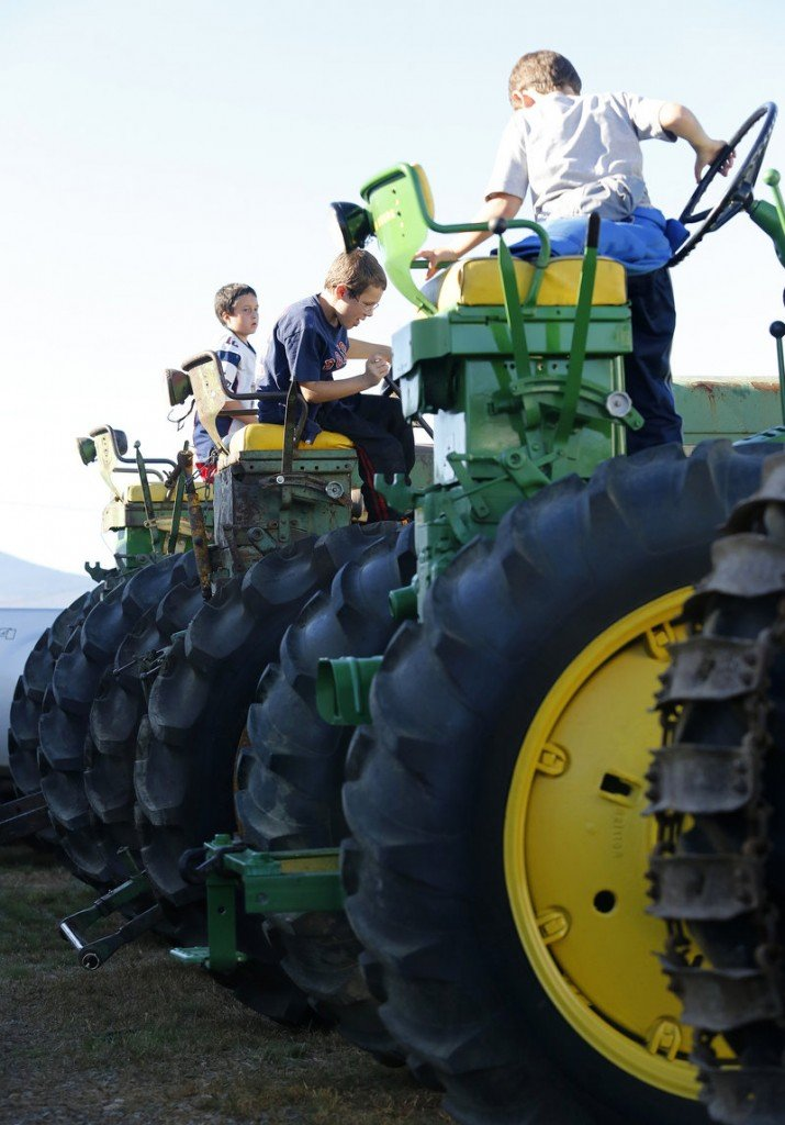 Children play on tractors displayed on opening day of the Fryeburg Fair on Sunday.
