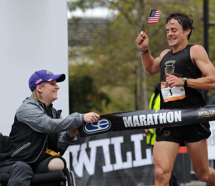 Boston Marathon bombing survivor Erika Brannock of Towson, Md., holds one end of the tape at the finish line as David Berden wins the Baltimore Marathon on Saturday.