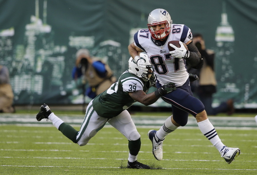 Rob Gronkowski tries to pull away from Antonio Allen after catching a first-down pass during the Patriots' only possession in overtime. After the drive fizzled, the Patriots punted and the Jets – aided by a penalty – kicked the winning field goal.