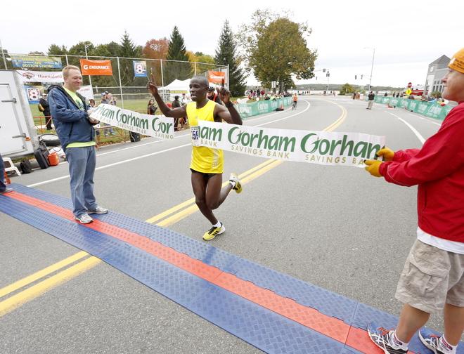Half-marathon winner Moninda Marube, 34, of Auburn crosses the finish line after winning the Maine half-marathon on Sunday in Portland.