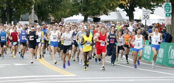 Runners take off at the start of Maine Marathon and half-marathon in Portland on Sunday. Rob Gomez, second from right, and Moninda Marube, in yellow at center, won the full and half-marathons respectively.
