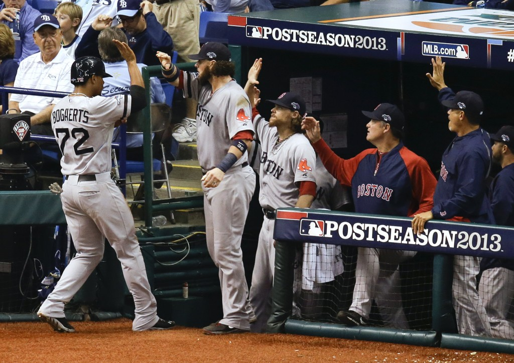 """Boston Red Sox's Xander Bogaerts (72) trades high-fives with teammates in the dugout after he scored in the seventh inning on a wild pitch by Tampa Bay Rays relief pitcher Joel Peralta in Game 4 of the division series Tuesday in St. Petersburg, Fla. """"He's very mature,"""" second baseman Dustin Pedroia said of his teammate."""