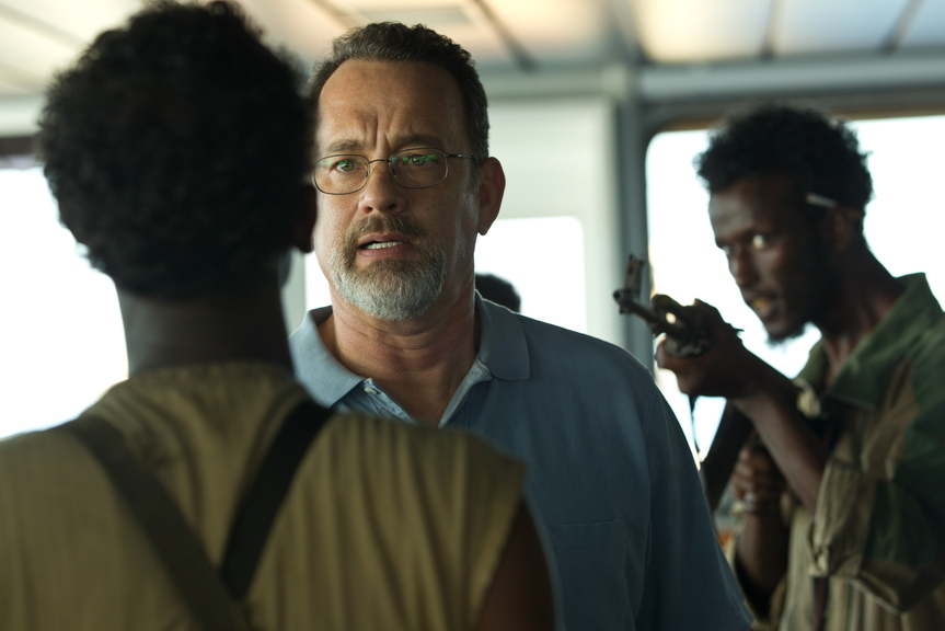 """Tom Hanks, center, deals with pirates in """"Captain Phillips,"""" a film dramatizing the 2009 attack on the M.V. Maersk Alabama off the coast of Africa. Directed by Paul Greengrass, the movie is good enough to keep viewers on the edge of their seats to the end even though they probably already know how it turns out."""