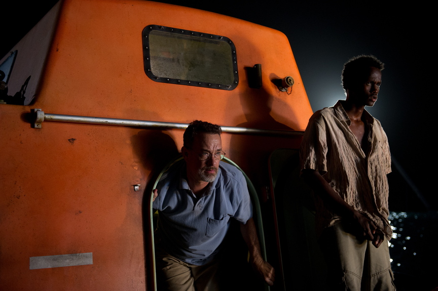 """Tom Hanks, left, and Barkhad Abdirahman star in """"Captain Phillips."""" Below, Hanks deals with pirates on his ship."""
