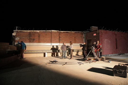 """Co-director Gary Robinov confers with actress Jennifer Porter on the set of """"Detour"""" while co-director Dean Merrill adjusts his framing and production assistant Andrea Nilosek operates a camera dolly. Writer Erin Enberg looks on."""