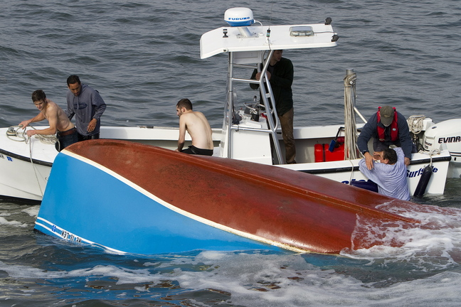 The last of the fishermen from the overturned boat is pulled aboard the Wells harbor master's boat Sunday.
