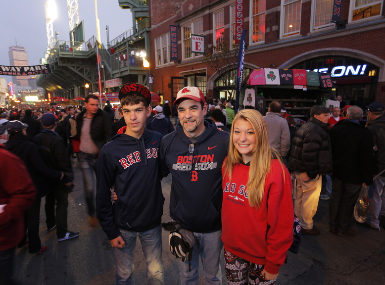"""Gabe Souza/Staff Photographer Lance Richmond of Pittsfield stands with his 14-year-old twins, Carter and Emily, on Landsdowne Street outside Fenway Park before the start of Game 6. """"We're all in,"""" Richmond said. """"The Red Sox are winning it tonight. We don't have tickets for Game 7."""""""