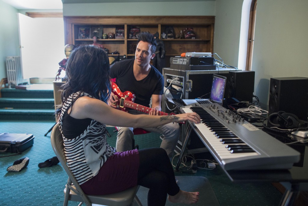 """In this July 22, 2013 photograph, married musicians Korey Cooper, left, and John Cooper of the Christian rock band Skillet play music inside of their home in Kenosha, Wis. Skillet released its eighth album """"Rise,"""" this June _ coming off its best-selling album """"Awake,"""" which went platinum after three years. (AP Photo/Scott Eisen)"""
