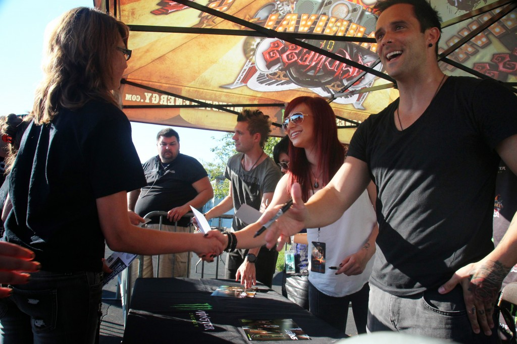 Members of the Christian rock band Skillet, from right, John Cooper, Jen Ledger, Korey Cooper and Seth Morrison, sign autographs for the fans they affectionately call panheads before a show in Chicago.