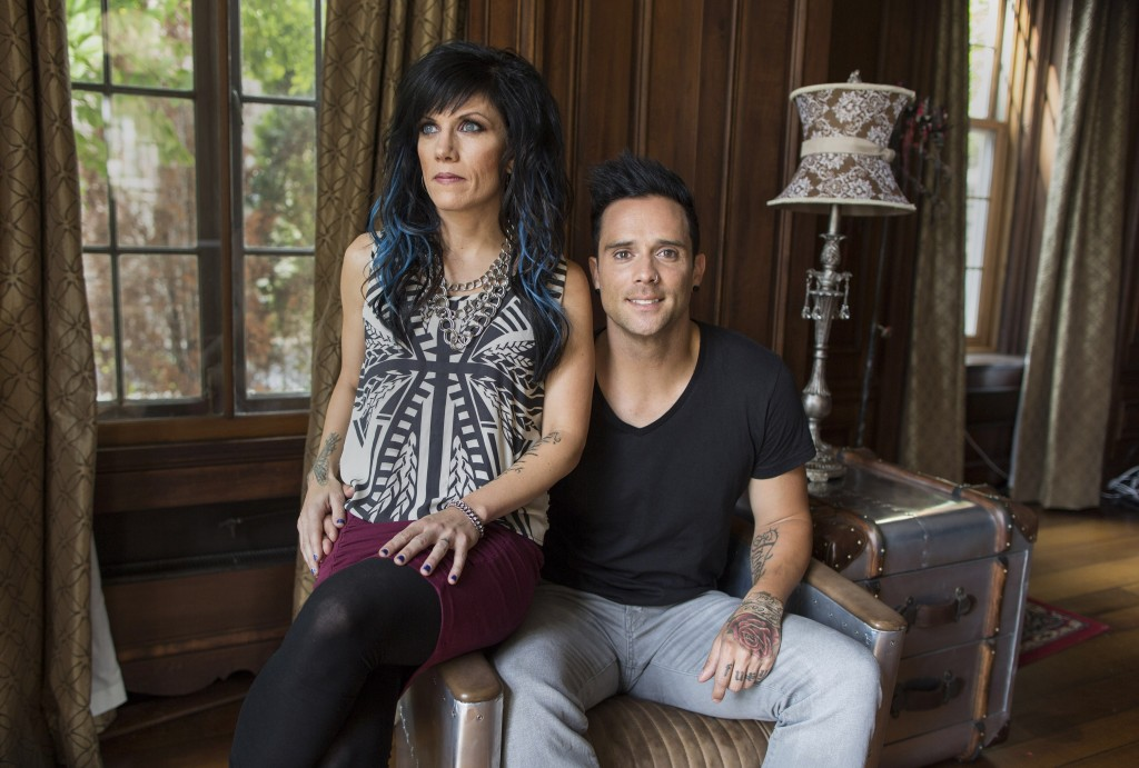 """In this July 22, 2013 photograph, married musicians Korey Cooper, left, and John Cooper of the Christian rock band Skillet pose for a portrait inside of their home in Kenosha, Wis. Skillet released its eighth album """"Rise,"""" this June _ coming off its best-selling album """"Awake,"""" which went platinum after three years. (AP Photo/Scott Eisen)"""