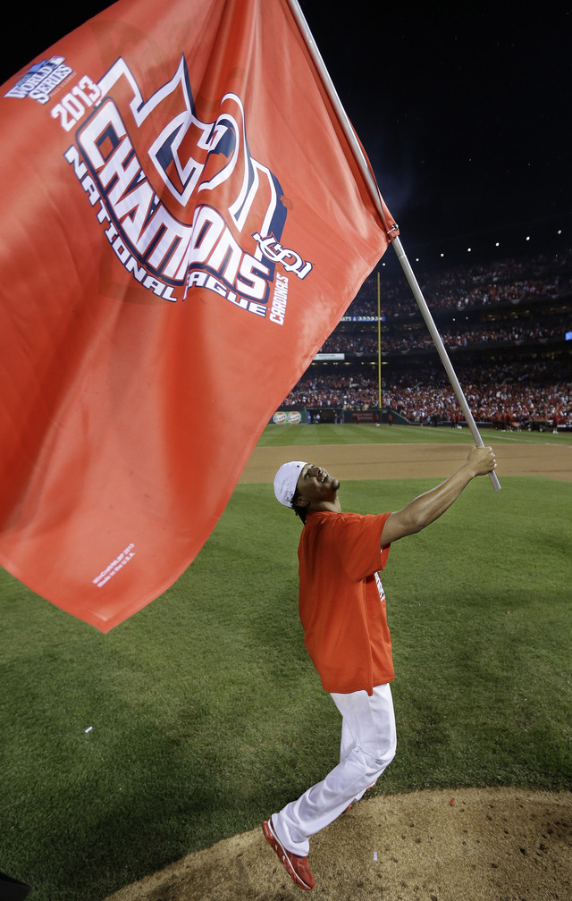 Rookie reliever Carlos Martinez, one of several young pitchers who have played key roles for the Cardinals, runs with a flag after St. Louis beat the Dodgers 9-0 Friday night to advance to the World Series..