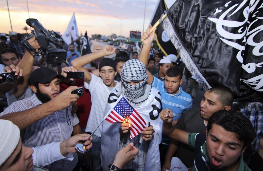 Dozens of supporters of the militant group, Ansar al-Shariah, burn an American flag and shout slogans denouncing the U.S. rendition of Nasih Abdul-Hamed al-Ruqai, who is also known as Abu Anas al-Libi, in Benghazi, Libya, on Monday.