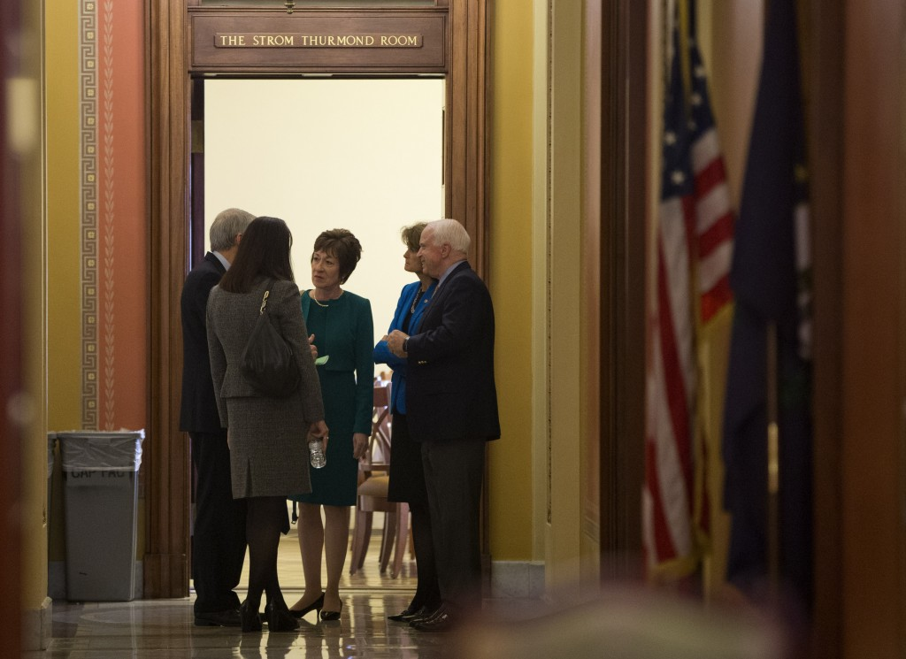 Sen. Susan Collins, R-Maine, center, talks with, from left, Sen. Rob Portman, R-Ohio, Sen.. Kelly Ayotte, R-N.H., Sen. Lisa Murkowski, R- Alaska, and Sen. John McCain, R- Ariz., on Capitol Hill in Washington on Friday. Republicans are offering to pass legislation to avert a default and end the 11-day partial government shutdown as part of a framework that would include cuts in benefit programs, officials said Friday.