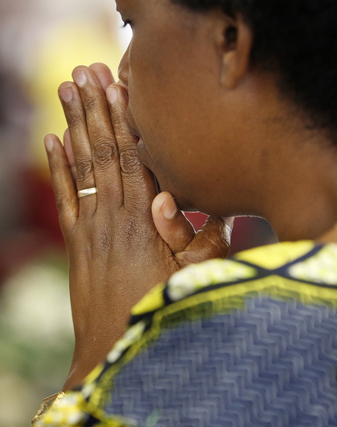 """A woman prays at the church filled with """"new Americans."""""""