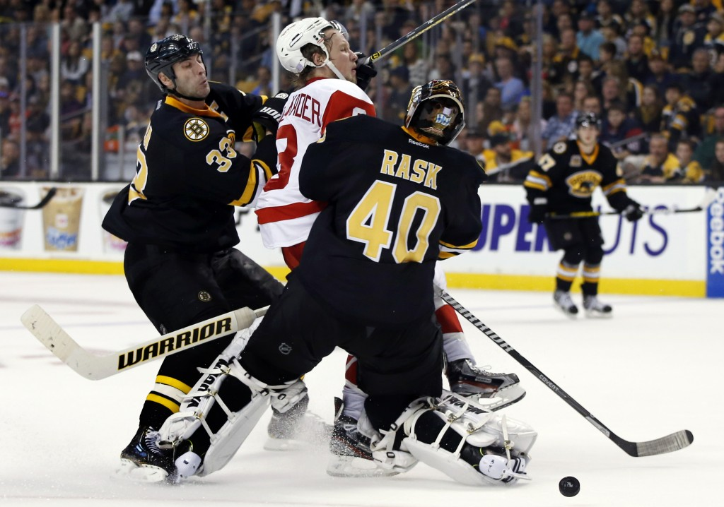 Boston Bruins center Chris Kelly (23) gets tangled up with Detroit Red Wings defenseman Jonathan Ericsson (52) as Red Wings center Pavel Datsyuk (13) watches them compete for the puck in the third period of an NHL hockey game in Boston, Monday, Oct. 14, 2013. The Red Wings won 3-2.