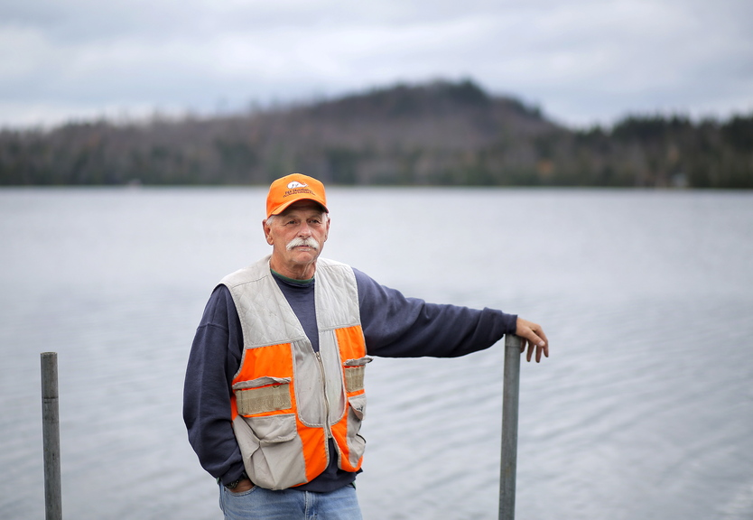 """Rodney Jones of Fort Fairfield stands on the dock of his wife's family's camp on Number Nine Lake in Township 9, Range 3 in central Aroostook County. Jones said he opposes a wind farm proposed by EDP Renewables. """"Nobody wants to see windmills along the lake,"""" he said."""