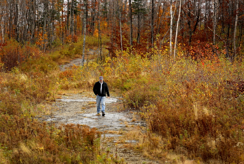 Dave Fowler, New England development director for First Wind, walks along a ridge in the Oakfield Hills this month. Thanks in part to a lucrative community benefits package, Oakfield has embraced plans by the company to build a 50-turbine wind farm scheduled to be online by 2015.