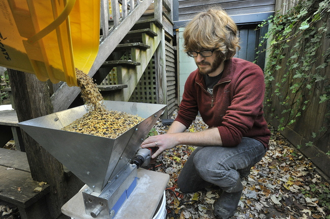 Craig Dilger grinds up freshly roasted barley that he will be using to brew his next batch of home brew.