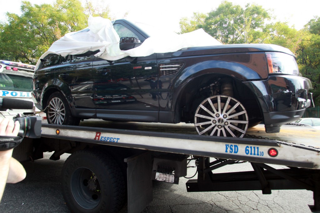 In this Oct. 5, 2013 file photo, The Range Rover involved in the bikers attack is moved from the police precinct for further police investigation in New York. An off-duty New York Police Department undercover detective apparently seen on video pounding on an SUV during a melee with motorcyclists has been arrested, Tuesday, Oct. 8, 2013.