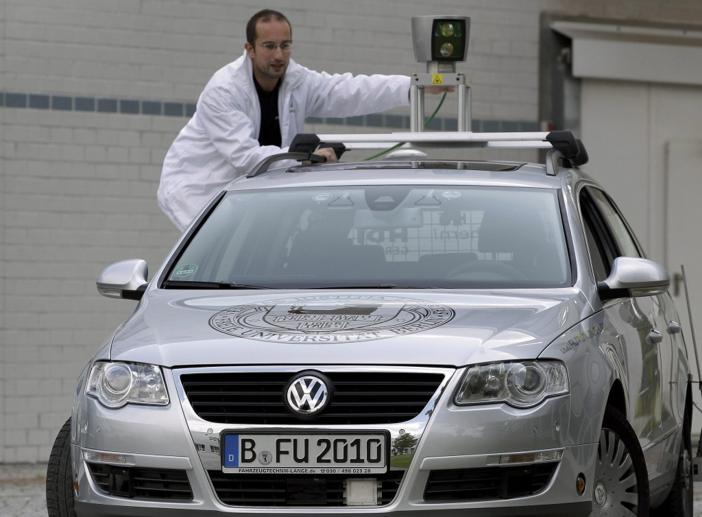 A technician in Germany adjusts a GPS on a Volkswagen capable of driving itself. General Motors, BMW, Toyota, Ford, Audi and others also have begun testing no-driver systems.