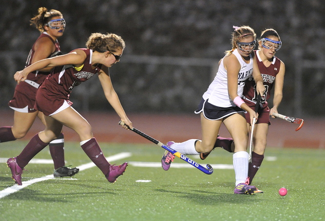 Haley Boydon of Yarmouth pushes the ball through the Freeport defense, including Abby Smith, right, in the first half of their Western Maine Conference field hockey game Tuesday at Yarmouth High.