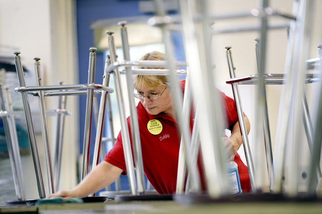 """Debby Bean, custodian at Scarborough Middle School, cleans desks in a classroom after the students have gone home for the day Monday. """"I would like the schools to stay safe and clean and keep the jobs local,"""" she says."""