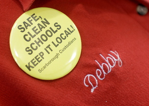 Bean wears a pin supporting Scarborough custodians as she cleans classrooms at Scarborough Middle School, where she has been night custodian for 12 years.