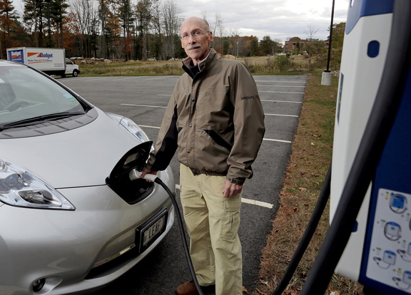 Marc Lausier, above, of Scarborough charges his Nissan Leaf, a fully electric car, at TideSmart Global in Falmouth on Friday. Gov. Paul LePage turned down Lausier's offer to test drive the car. The photo at top shows the front end of the electric charger.