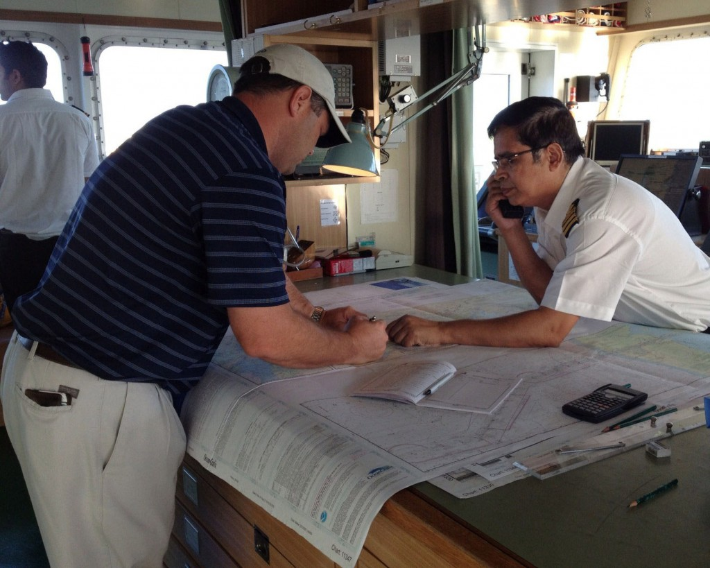 Mariners use a printed nautical chart aboard their ship.