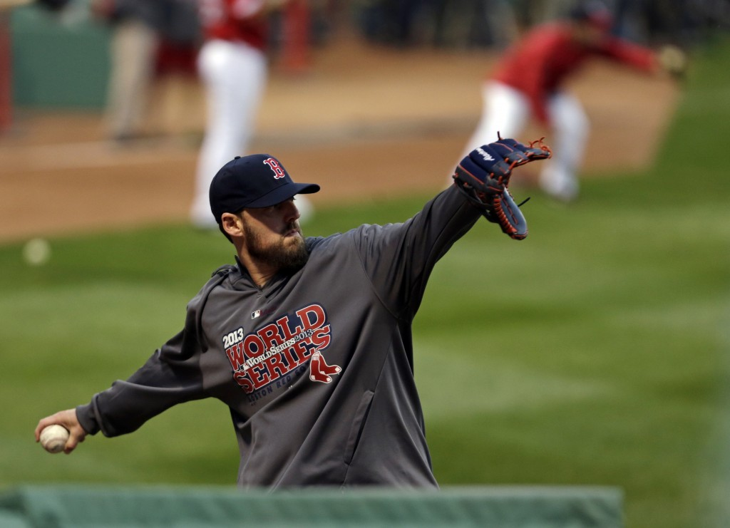 Boston Red Sox pitcher John Lackey throws during a baseball workout Tuesday in Boston. The Red Sox are scheduled to host the St. Louis Cardinals in Game 1 of baseball's World Series on Wednesday.
