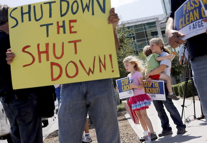 As the federal government shutdown continues, Tory Anderson, right, with her kids Audrey, 7, and Kai, 3, of Goodyear, Ariz., join others as they rally for the Alliance of Retired Americans to end the shutdown in front of the Social Security Administration offices on Wednesday, Oct. 9, 2013, in Phoenix. Other groups rallying to end the government shutdown include Professional Aviation Safety Specialists, the American Federation of Government Employees AFL-CIO, and Arizona FairShare.