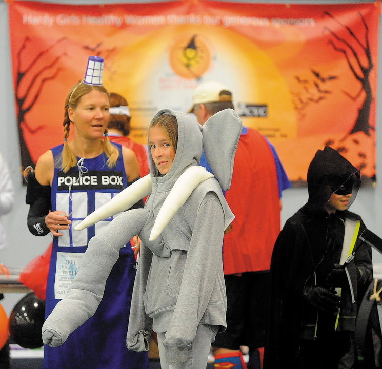 """Alison Stabins, 11, center, dressed as an elephant, and her mother, Amy, dressed as Tardis from """"Dr. Who,"""" await the start of the Freaky 5K Fun Run sponsored last Saturday by Hardy Girls Healthy Women at Colby College in Waterville. The event was organized to encourage girls to come up with creative and scary Halloween costumes instead of stereotypical or sexually overt ones."""
