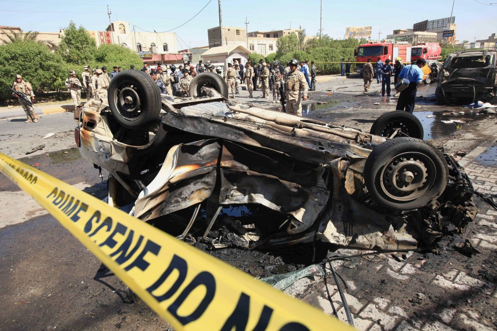 Security forces inspect the site of a car-bomb attack in Basra, 340 miles southeast of Baghdad, Iraq, Sunday. A string of bombings in mostly Shiite-majority cities across Iraq on Sunday killed and wounded dozens of people.