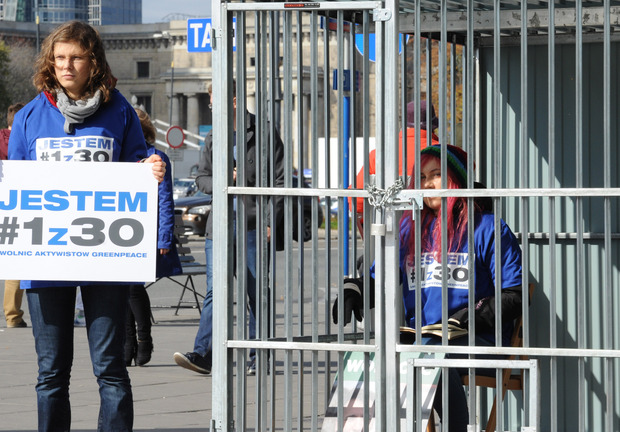 """One Greenpeace activist sits in a cage in Warsaw, Poland, while another one holds a placard reading """"I am 1 of the 30"""" in a protest against Russia's jailing of Greenpeace activists."""