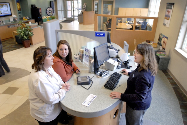 Teresa Webber and Jennifer Coyne conduct business with Heather Hatt in May 2009 at Town & Country Federal Credit Union in Scarborough.