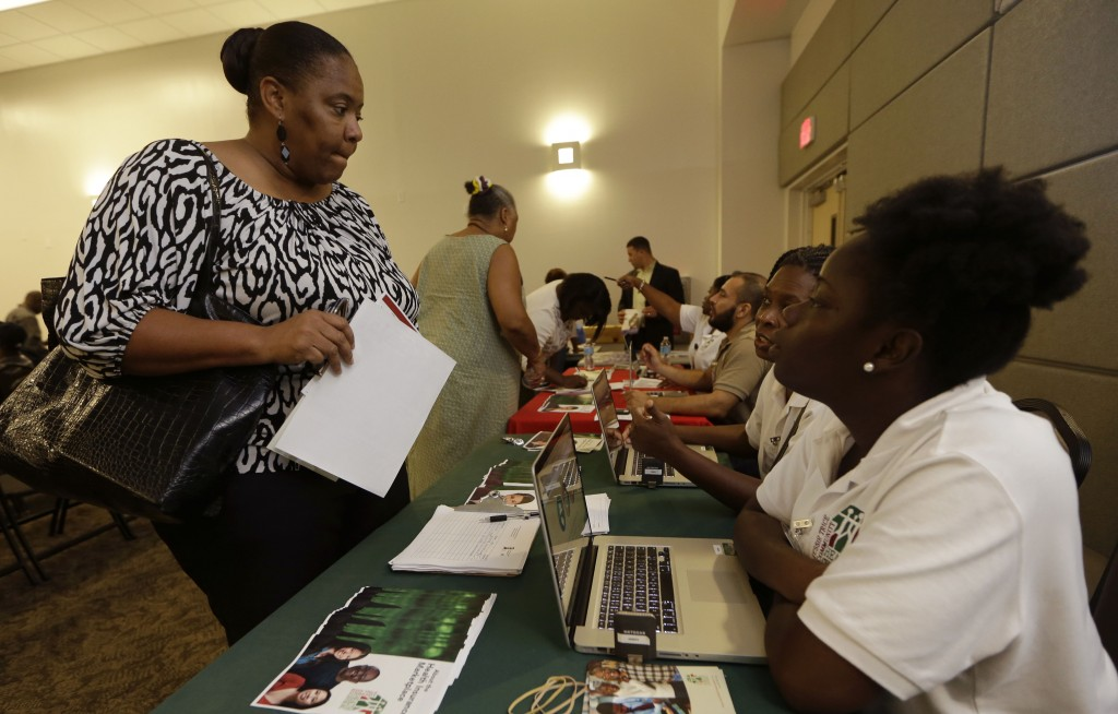 Velicia Martin talks with employees of the Jesse Trice Community Center about insurance options under President Obama's health care law in Miami Gardens, Fla., Thursday. technology problems with a federal government website, many were unable to enroll online for the first few days of the program.