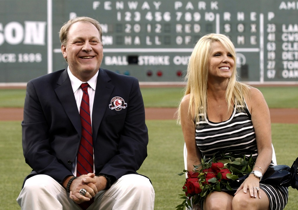 In this Aug. 3, 2012 file photo, former Boston Red Sox pitcher Curt Schilling sits with his wife Shonda, right, after being introduced as a new member of the Red Sox Hall of Fame before a baseball game between the Red Sox and the Minnesota Twins at Fenway Park in Boston. Schilling, whose video game company collapsed into bankruptcy, is selling off furniture, sports collectibles and even artificial plants from his Massachusetts home. An estate sale company has scheduled a sale of items from Schilling's seven-bedroom, 8,000-square-foot Medfield residence for Saturday, Oct. 12, 2013.