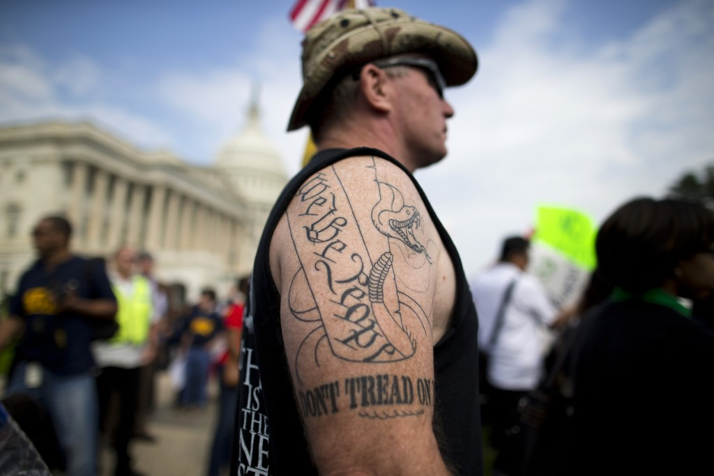 Tea party supporter Greg Cummings of Cincinnati, Ohio, watches a rally with the Democratic Progressive Caucus and furloughed federal employees against House Republicans on Capitol Hill in Washington on Friday. Cummings attended the rally to blame Senate Democrats for the government shutdown.