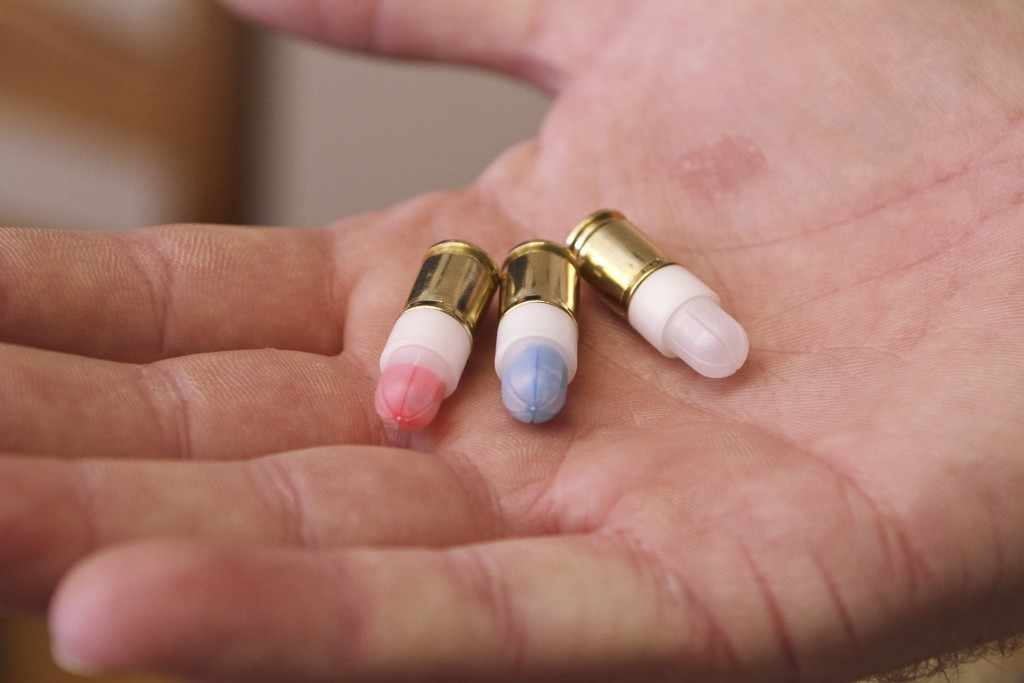 Firearms safety instructor Andrew Hyduchak displays nonlethal Simunition ammunition filled with powder that can mark targets with different colors at Prepare to Act firearms safety training facility, in Watertown, Conn. The facility is in a 2,000-square-foot structure set up to train gun owners in home invasion scenarios using the Simunition ammunition.