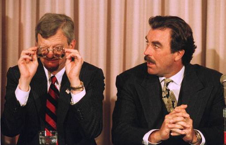 Author Tom Clancy, left, adjusts his glasses as actor Tom Selleck looks on, in this 1994 photo.